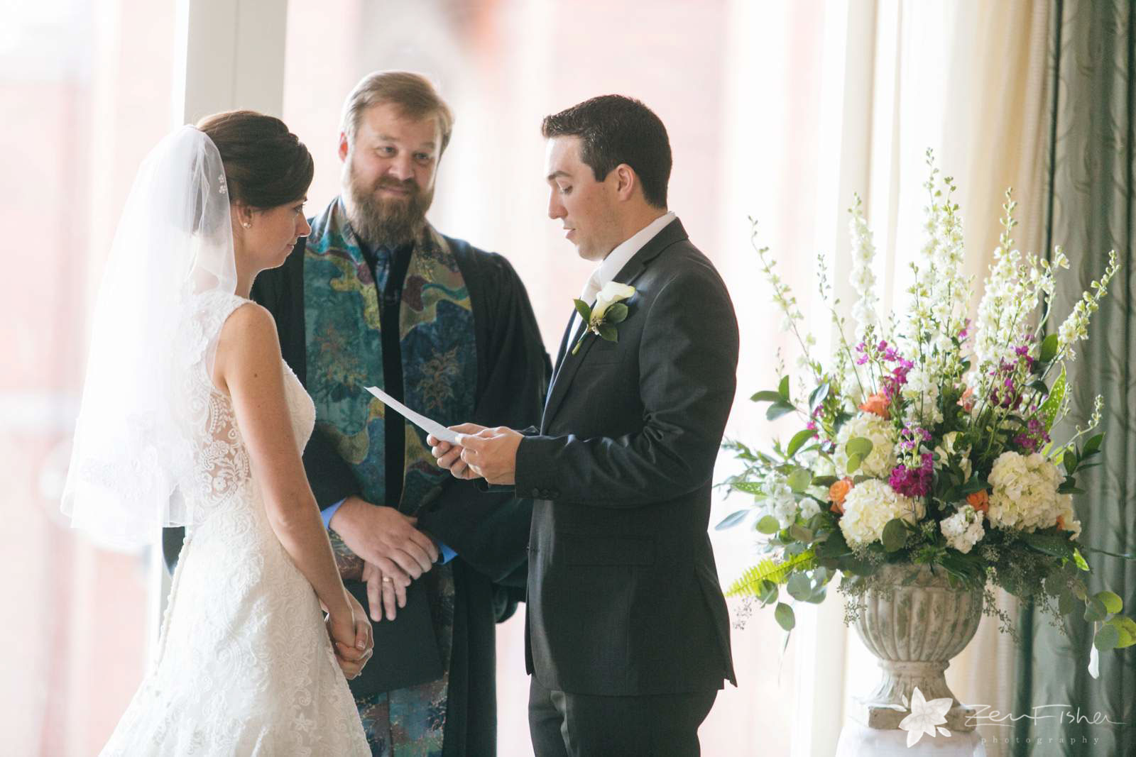 Groom saying his vows during wedding ceremony, beautiful natural light.