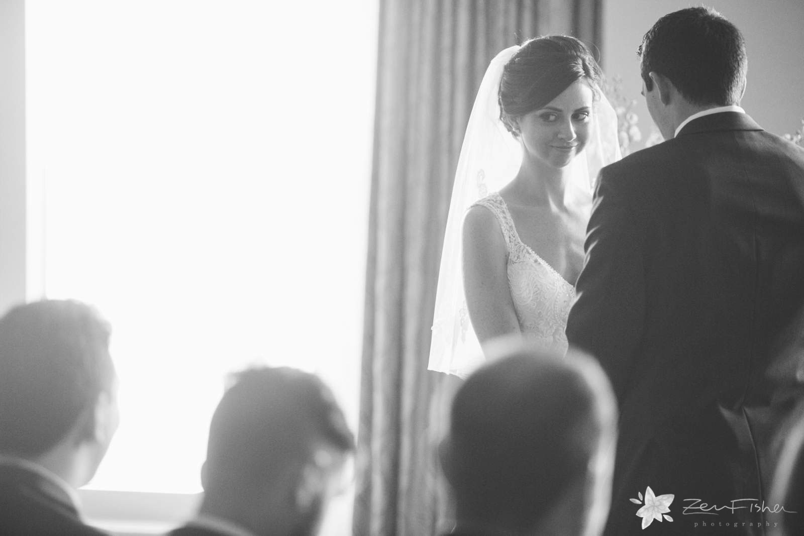 Bride's reaction to groom's vows, bride smiles at wedding guests during ceremony, black and white