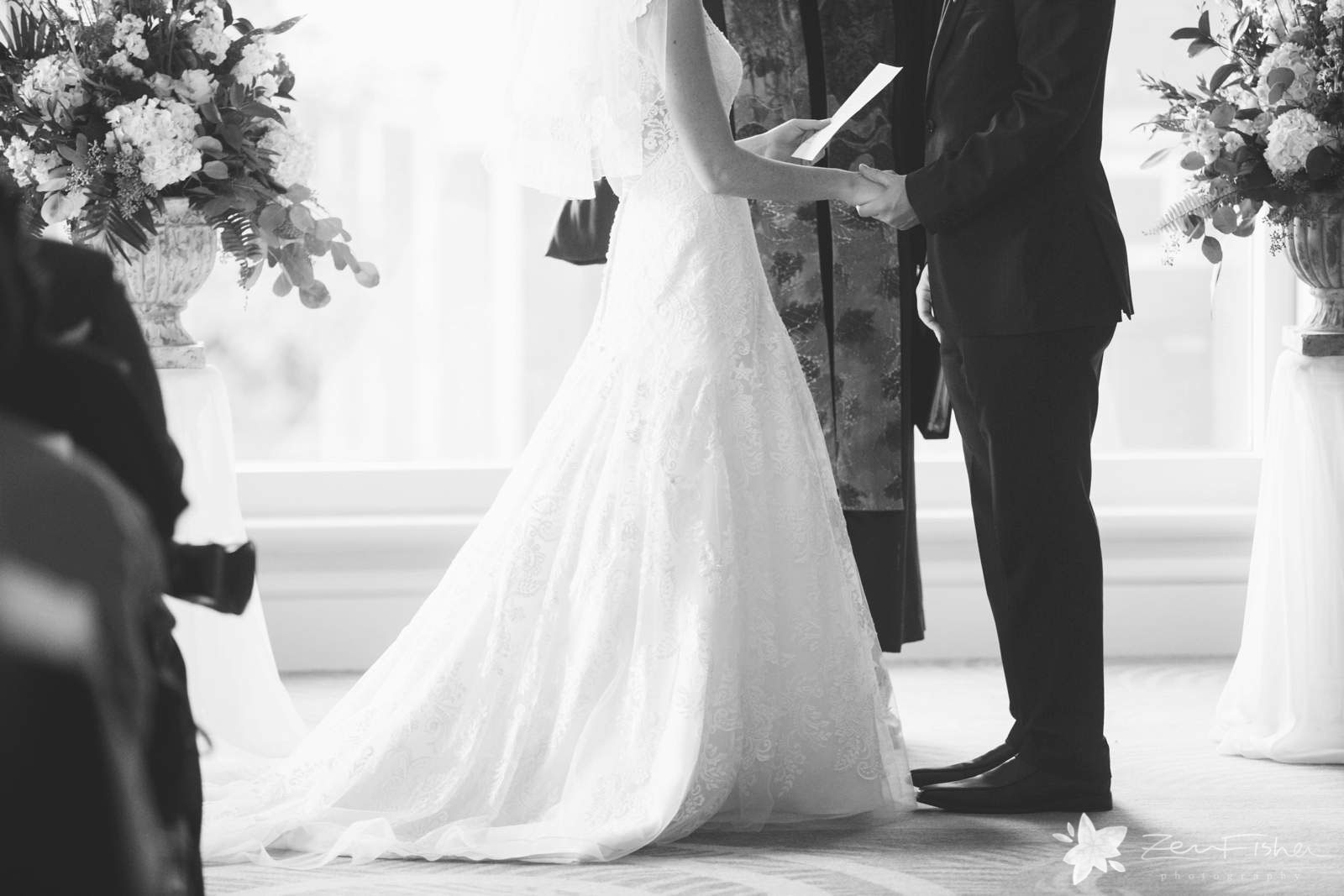 Bride and groom holding hands during ceremony, black and white, beautiful natural light