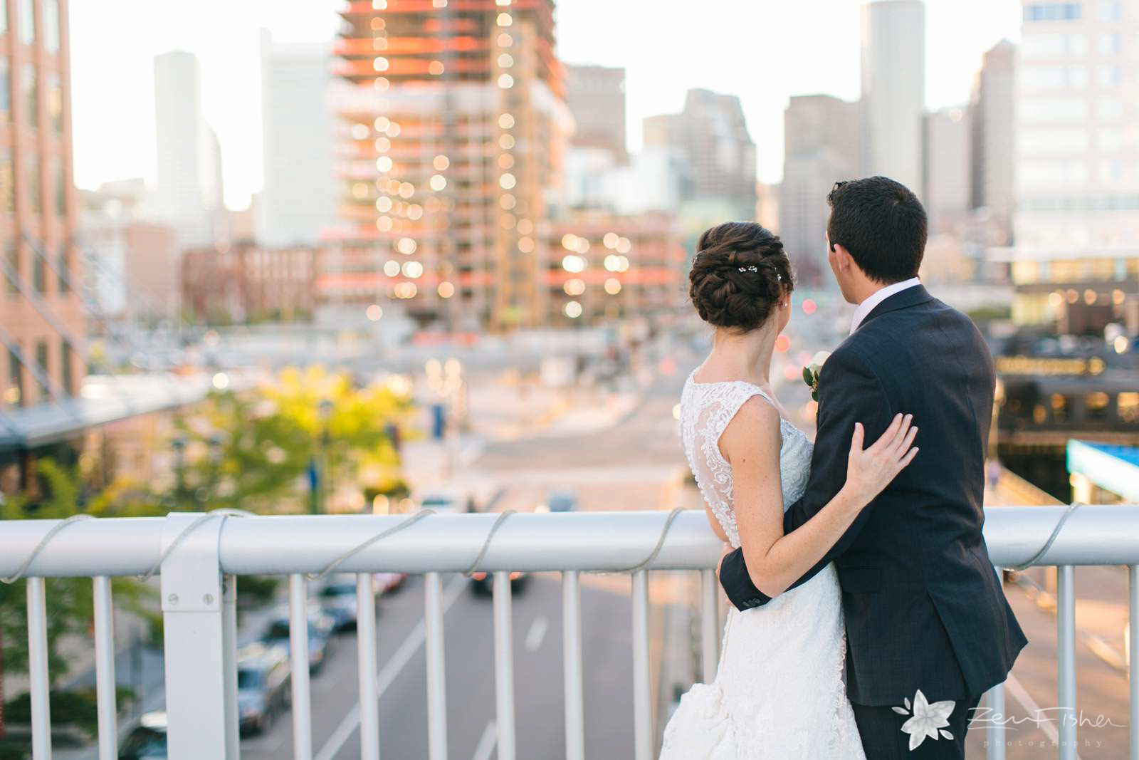 Bride and groom portrait standing on bridge looking out at view of fort point neighborhood in Boston