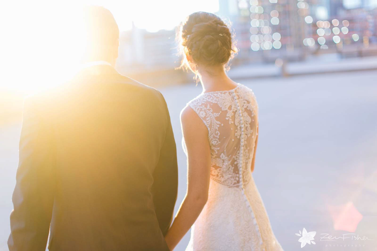 bride and groom holding hands and walking during sunset with ethereal light