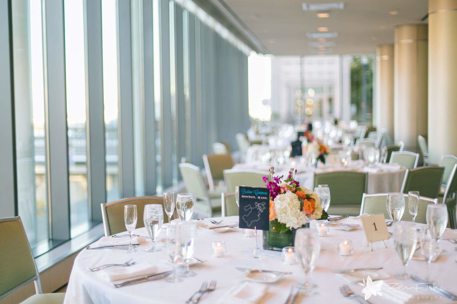 Reception hall with table settings at Boston Seaport Hotel with tall windows and airy natural light.
