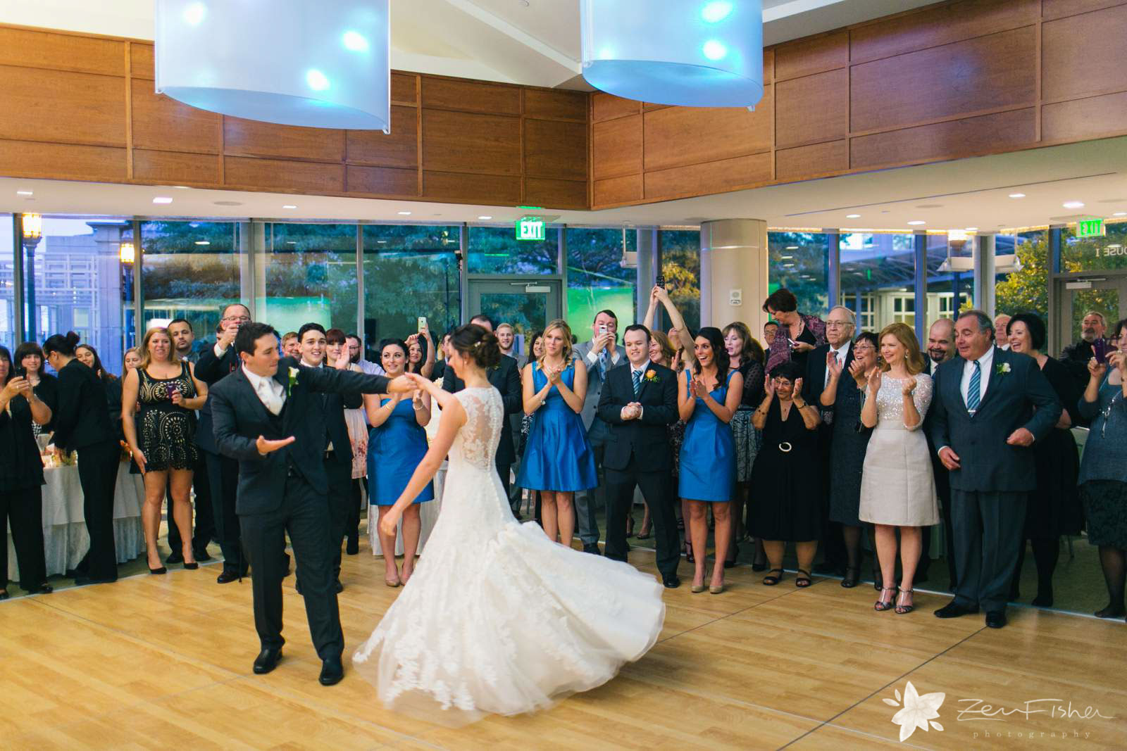 Groom spins bride during first dance, bride's dress spinning, wedding guests watching first dance