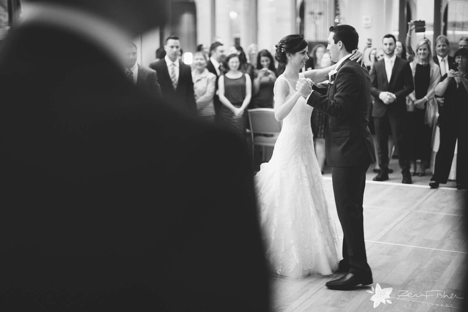 Bride and groom looking into each other's eyes, peeking over guest's shoulder to watch first dance.