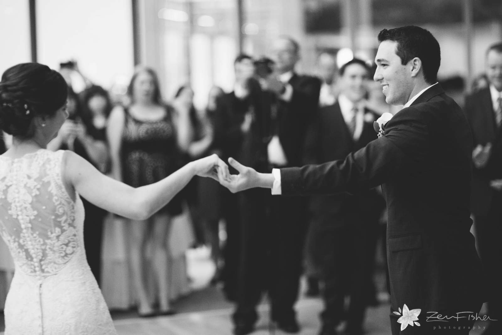 Bride and groom dancing during first dance, groom smiling at bride, black and white.