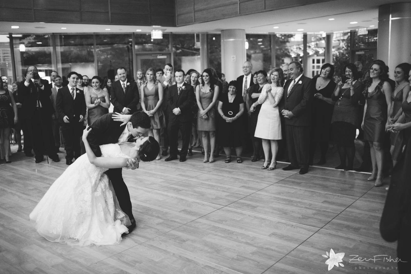 Epic shot of Groom dipping bride during first dance, black and white, guest reaction to first dance