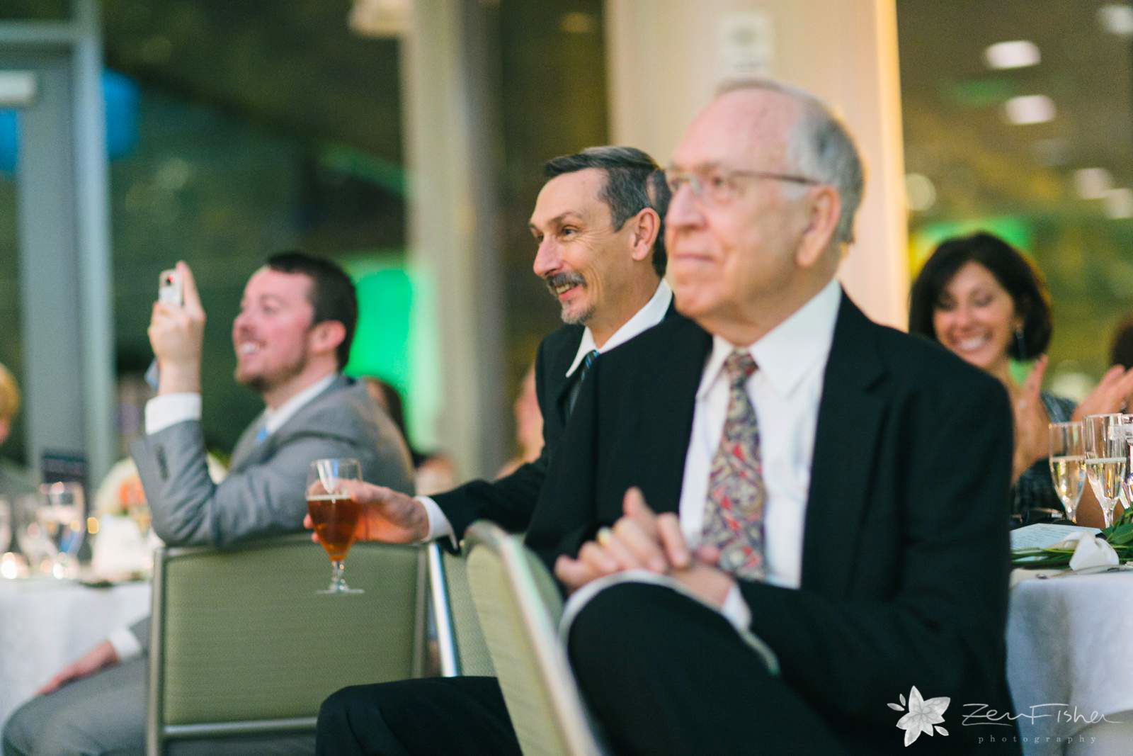 Father of the groom reacting to toasts during wedding reception.