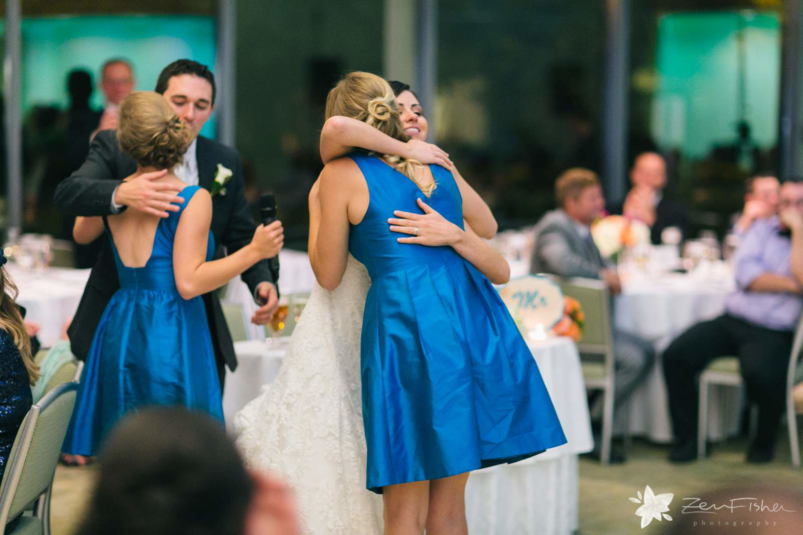 Bride and groom hugging bridesmaids after giving their toasts.