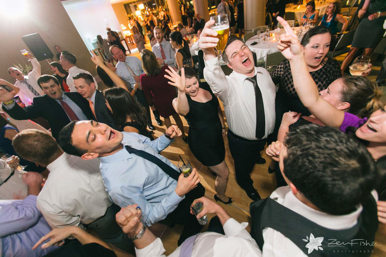 Epic shot from above of wedding guests shouting and dancing on the dance floor with lots of energy.