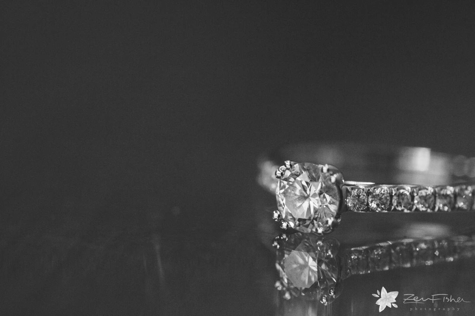 Detail of engagement ring, reflections on the table, black and white