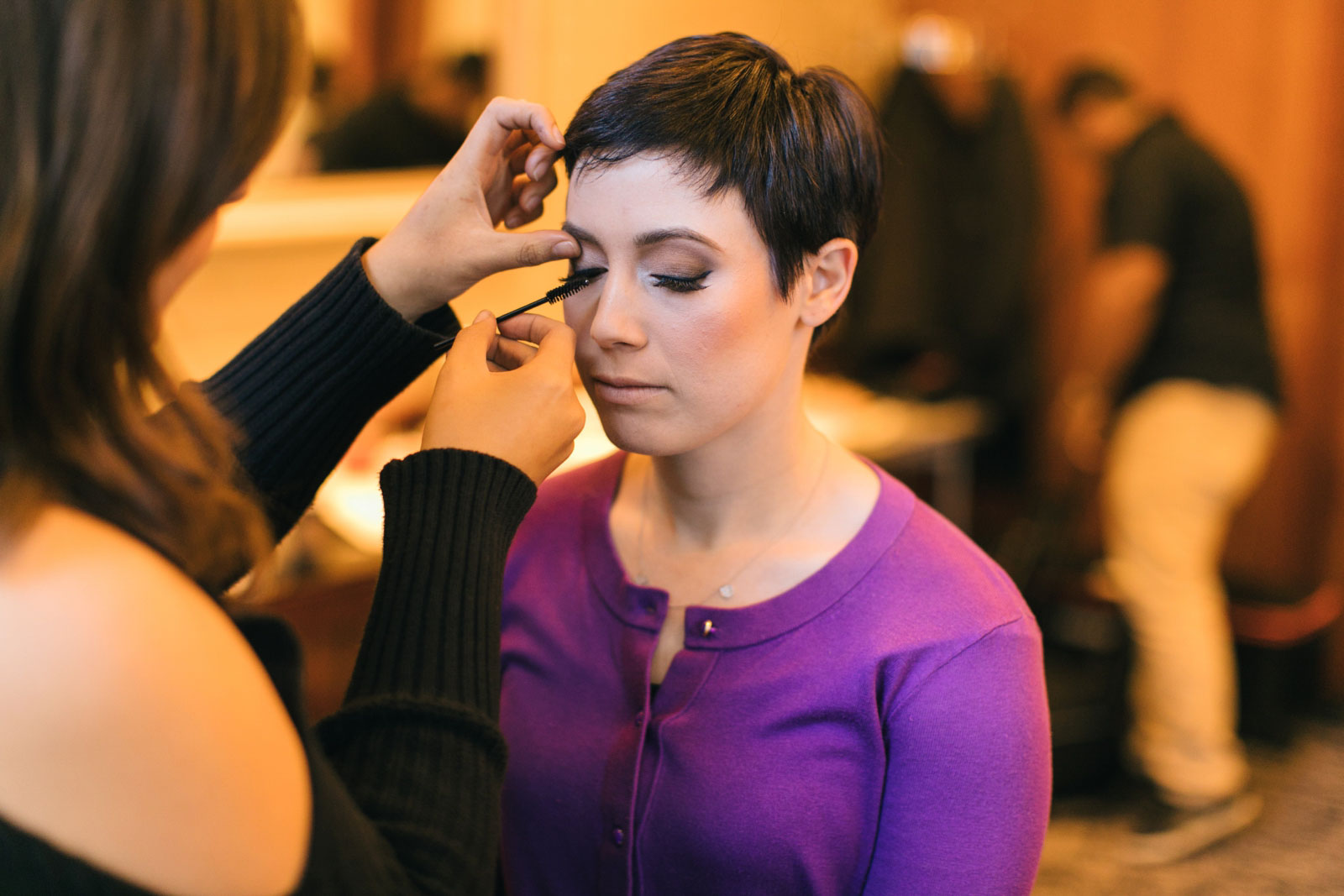 bride with pixie cut getting her make up done in bridal suite at Ritz-Carlton Boston
