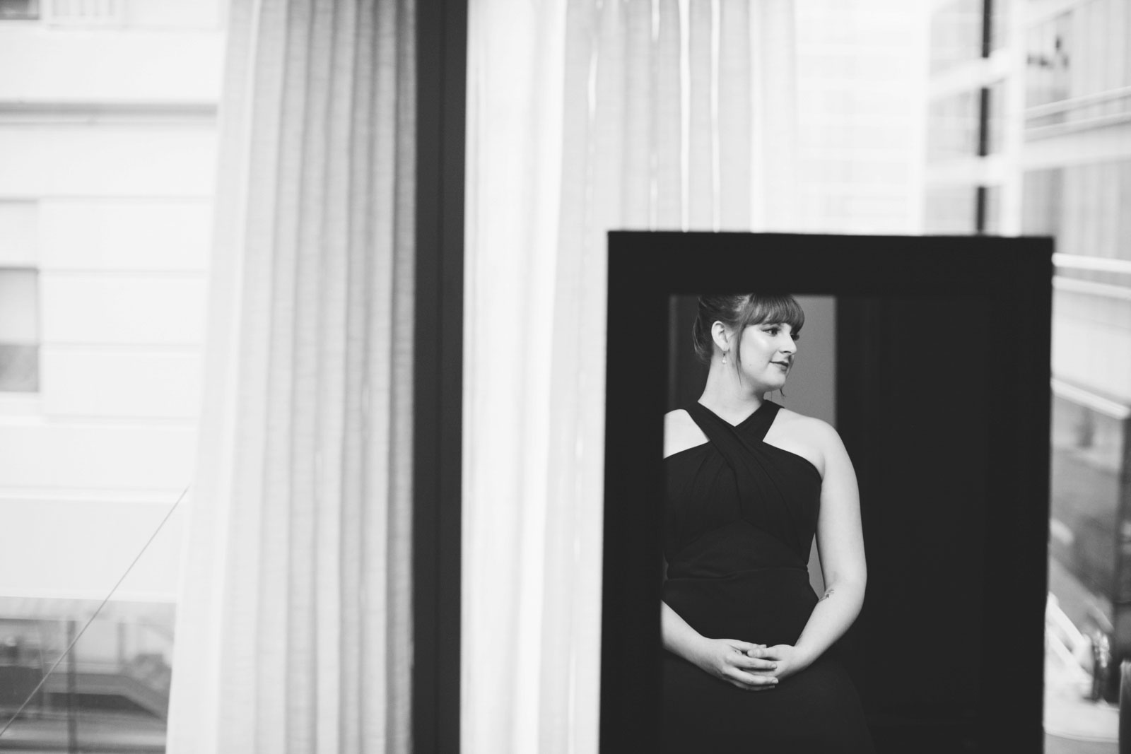 Blank and white shot of bridesmaid in reflection of mirror in bridal suite at the Ritz-Carlton