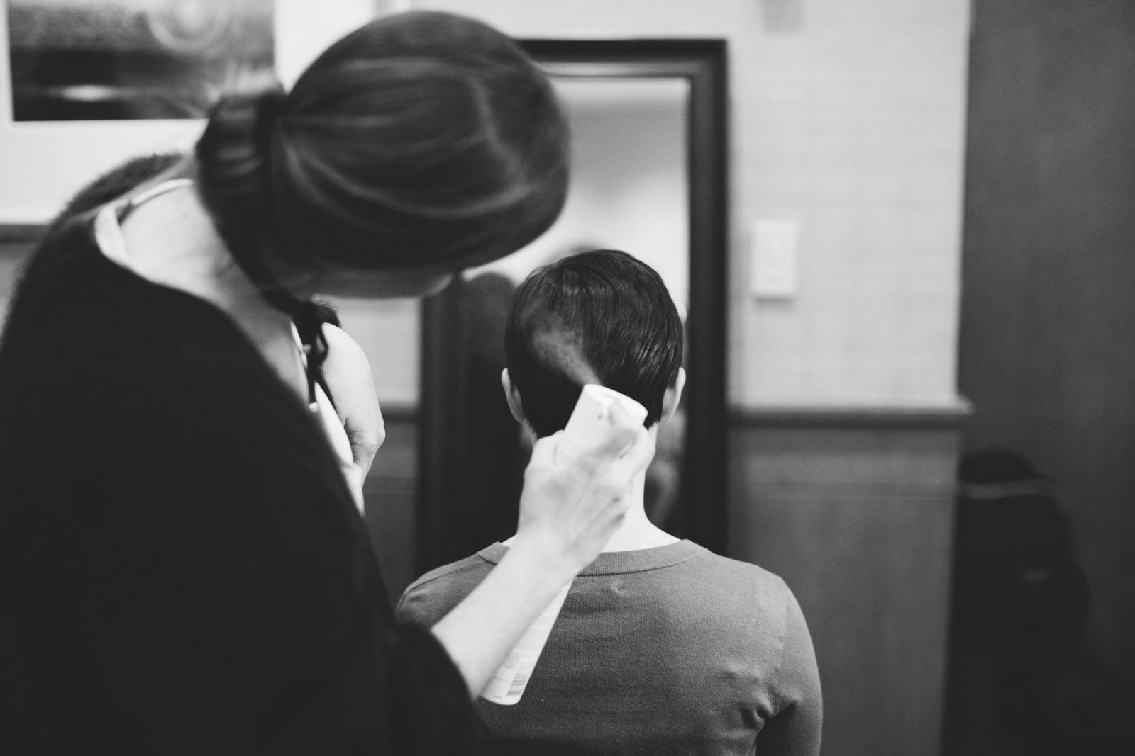 black and white shot of bride getting hair done in bridal suite, bridal hair pixie cut