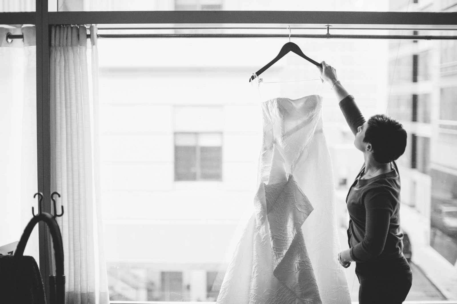 Black and white silhouette of bride taking down wedding dress from hanger in front of window