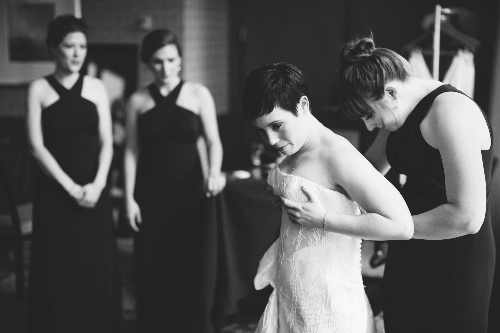 moody black and white shot of maid of honor helping bride into her asymmetrical wedding dress