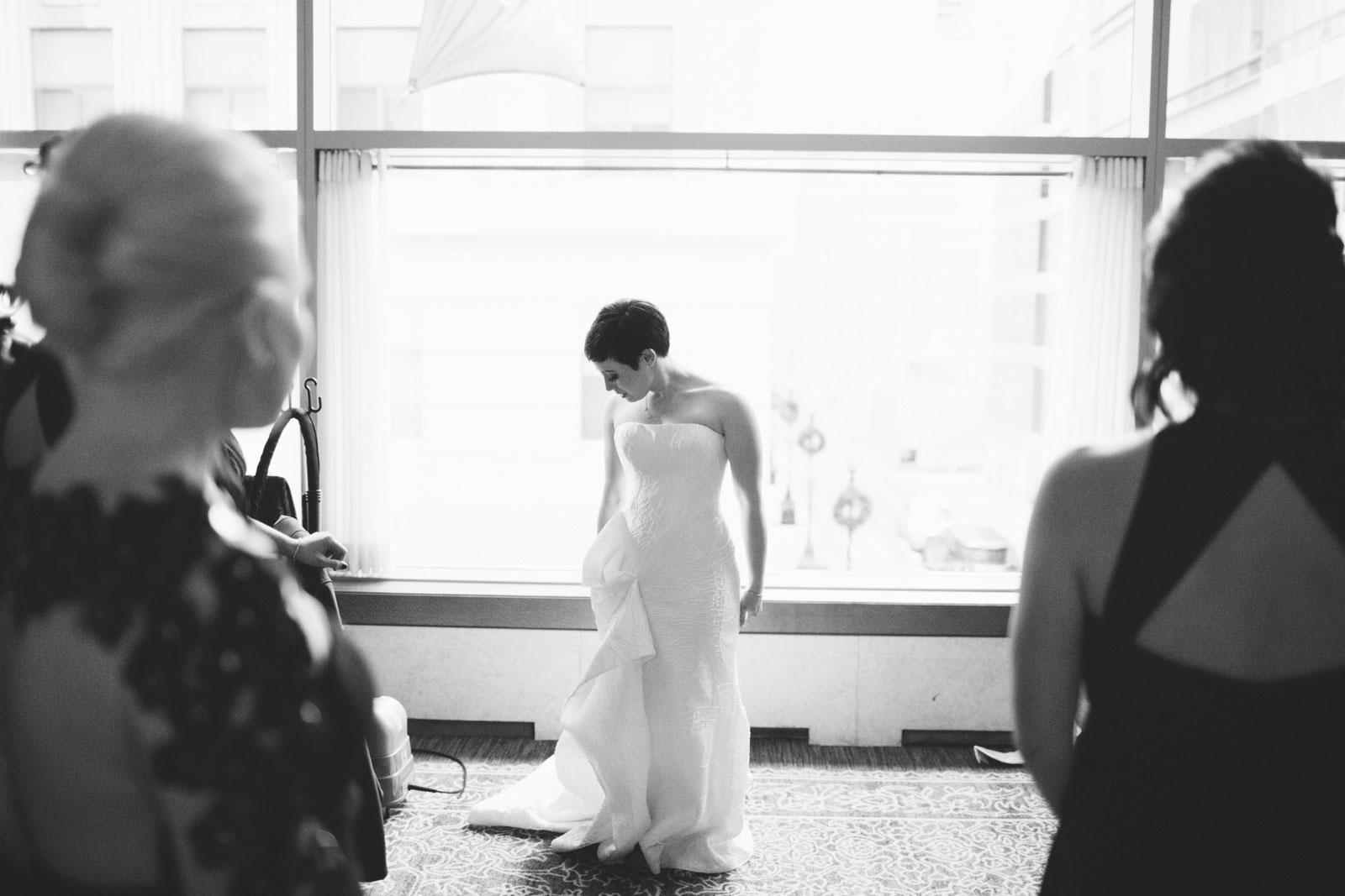 black and white silhouette of bride in asymmetrical wedding dress standing in front of window