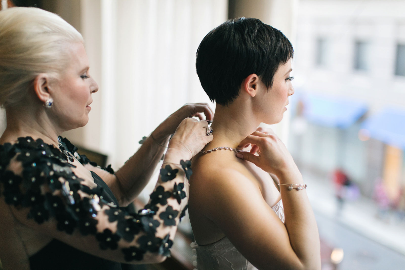 Mother of the bride helping the bride with her necklace while getting ready in bridal suite at Ritz