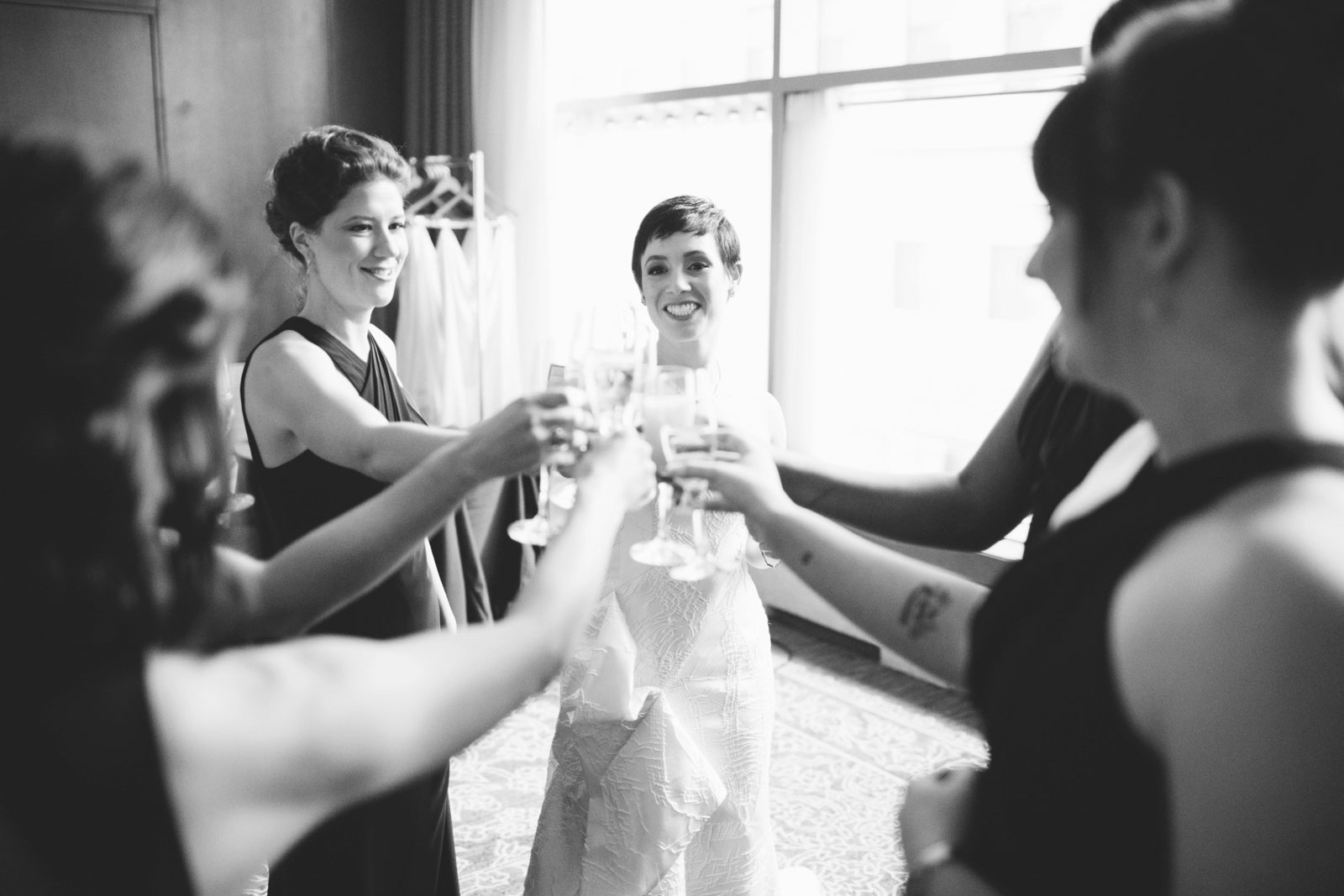 black and white shot of bride and bridesmaids sharing a champagne toast in bridal suite