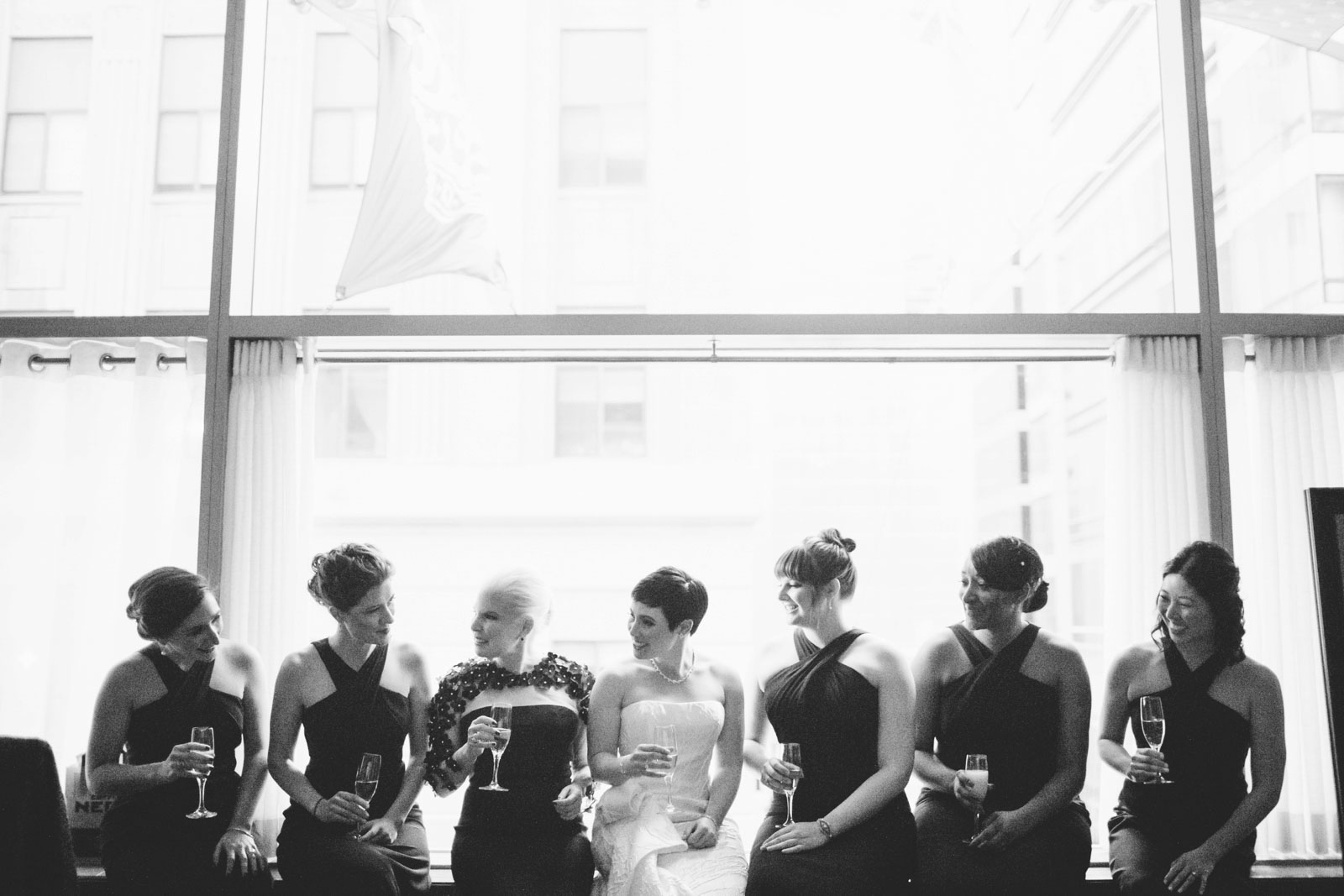 Black and white silhouette of bridal party sitting on window sill sipping champagne in bridal suite