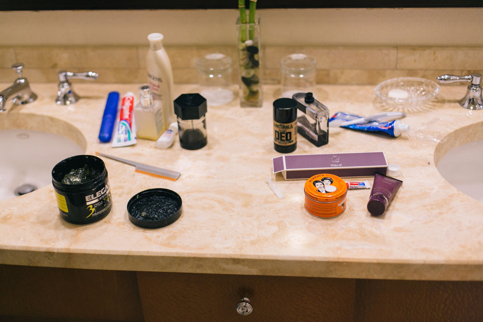 groomsmen's hair products on counter in bathroom while groomsmen get ready at Ritz-Carlton