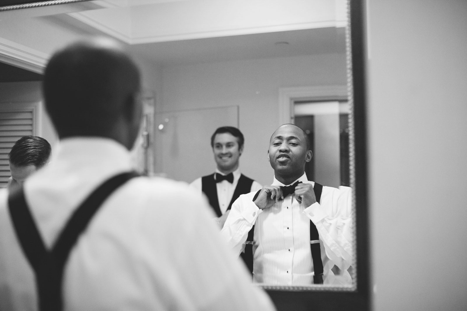 black and white shot of groom fixing his bow tie in mirror in hotel suite at Ritz-Carlton