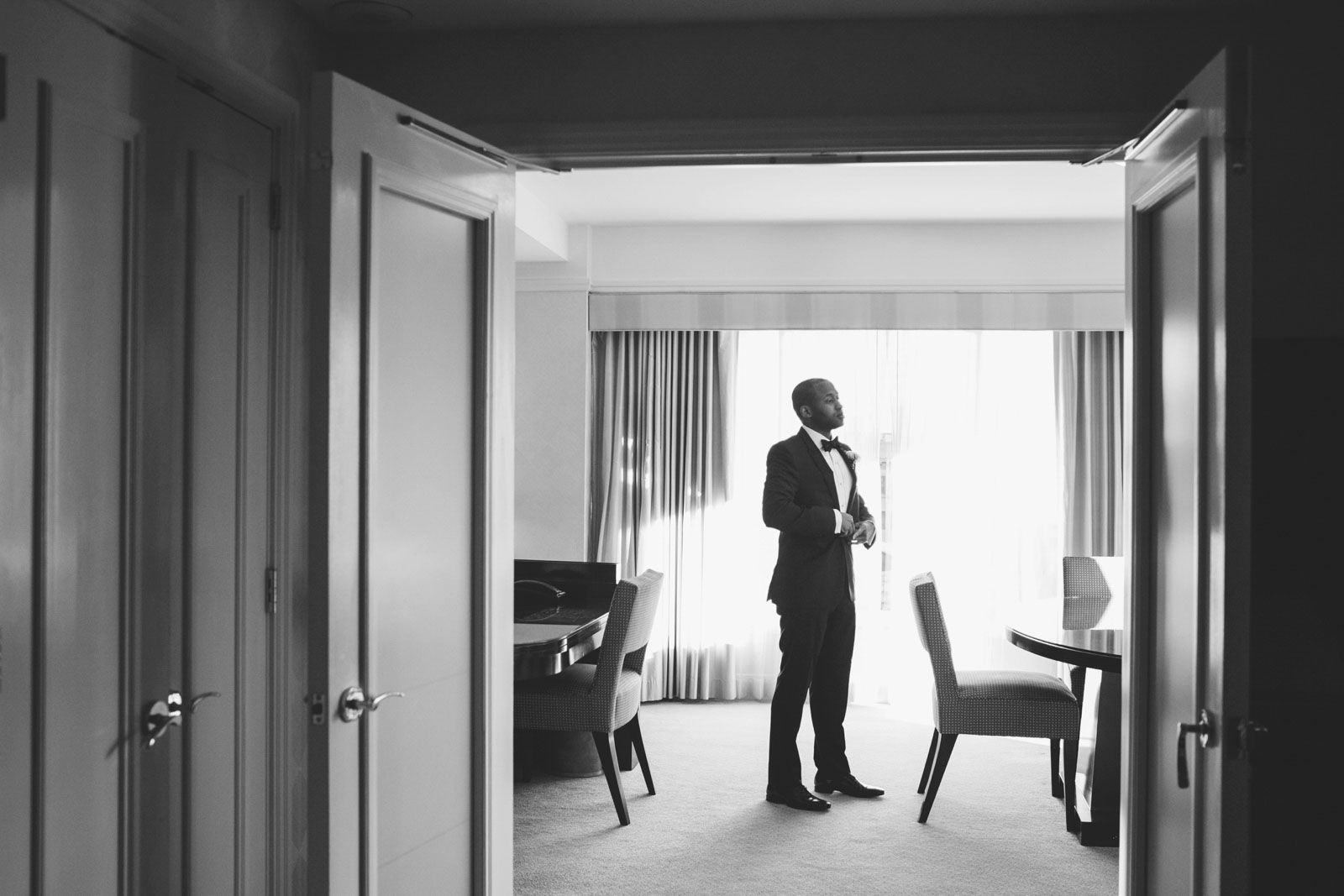 black and white shot of groom getting ready with natural window light in hotel suite at Ritz-Carlton