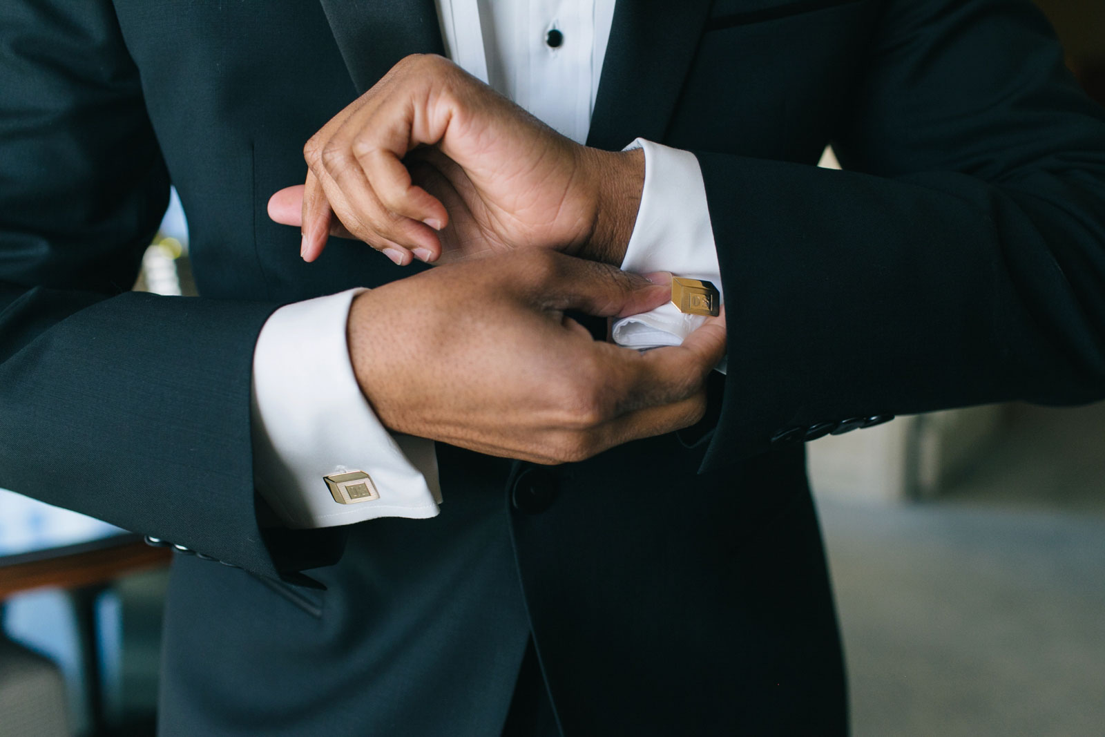 groom fixing his heirloom gold cufflinks while getting ready in hotel suite at Ritz-Carlton Boston
