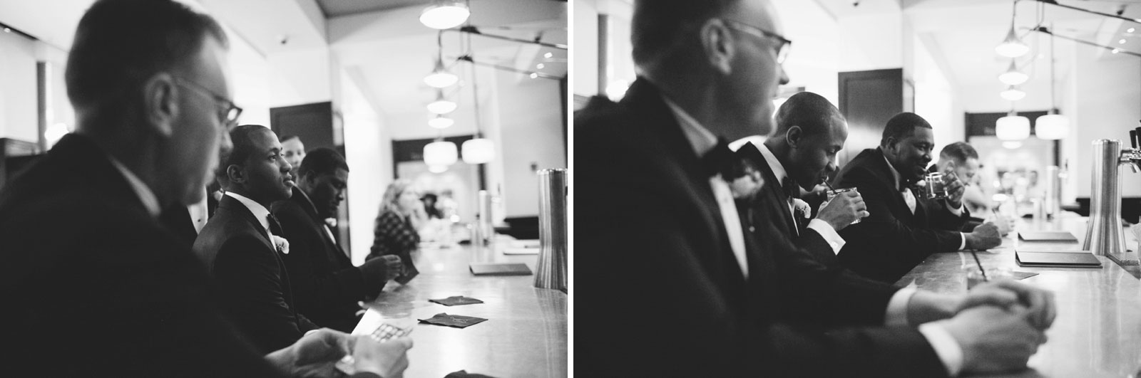 black and white shots of groomsmen ordering drinks at the hotel bar at the Ritz-Carlton Boston