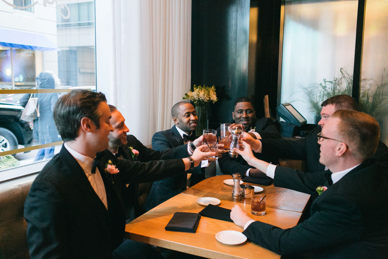 Groom and groomsmen sharing a toast at the hotel bar at the Ritz-Carlton Boston.