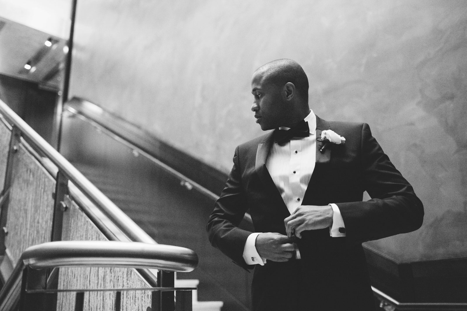 black and white groom portrait putting his jacket and waiting on staircase for his bride