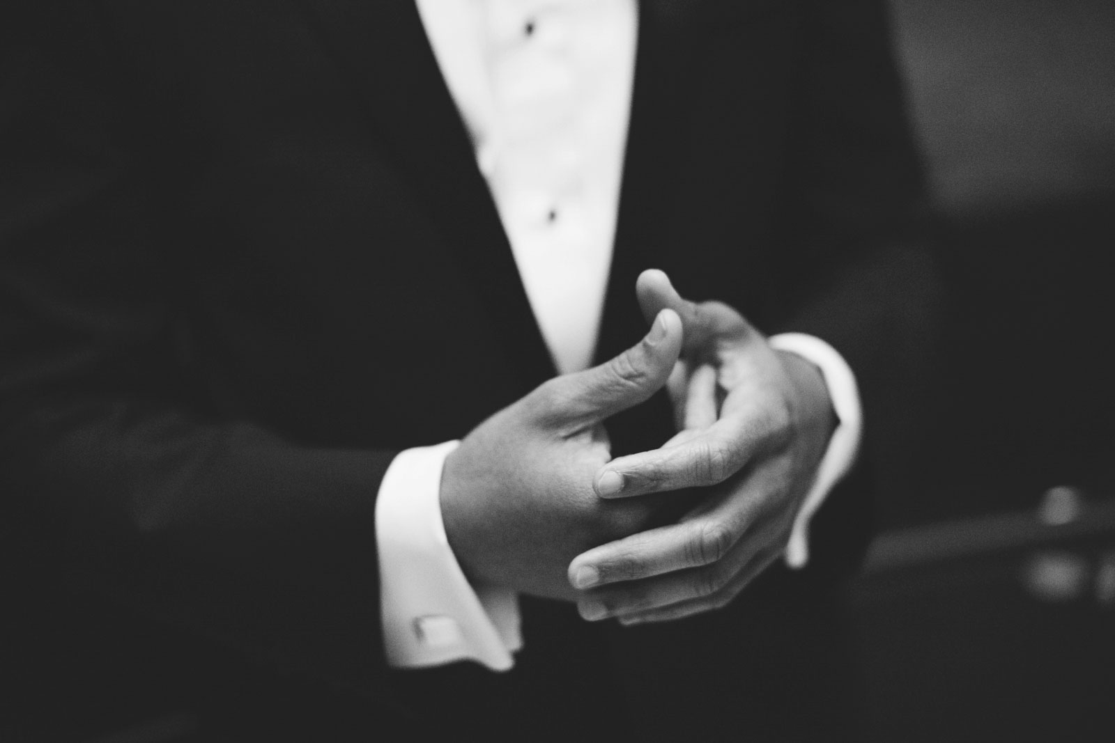 black and white shot of grooms hands while he waits patiently for bride to arrive for the first look