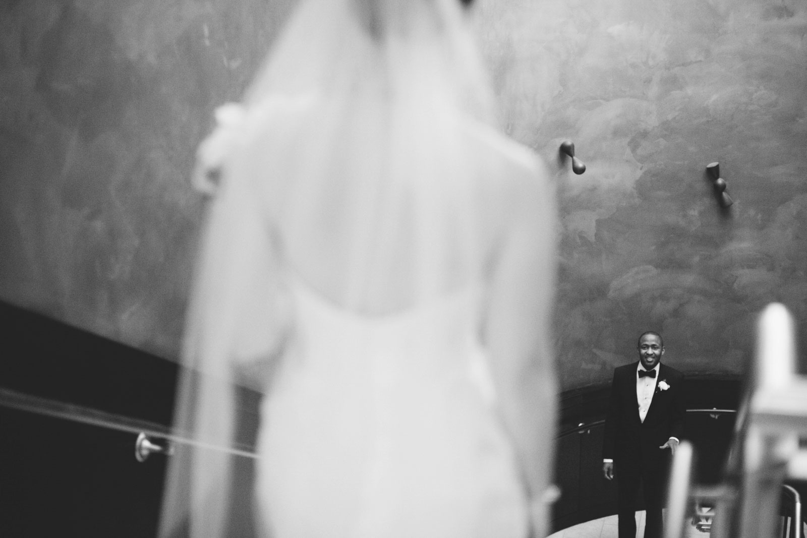 bride stands at the top of the stairs as groom smiles at seeing bride for the first time