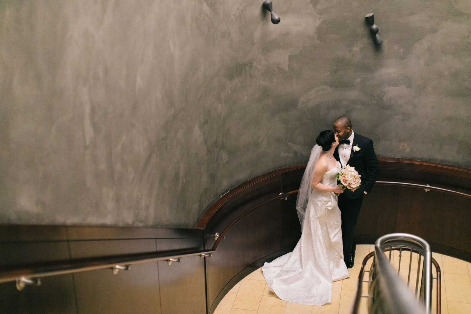 bride and groom kiss on grand staircase for their first look at Ritz-Carlton Boston