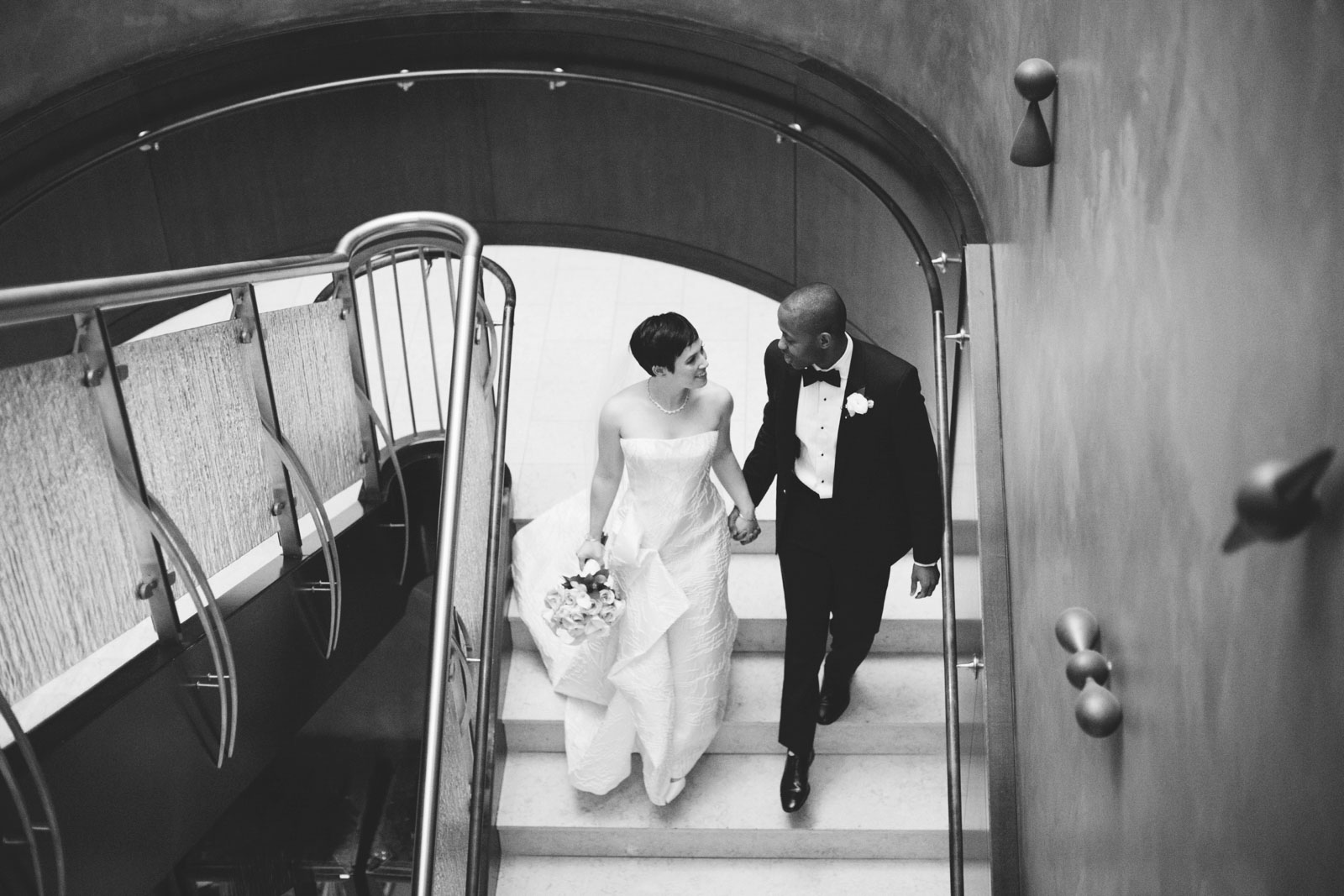 black and white candid portrait of couple walking down stairs holding hands during first look
