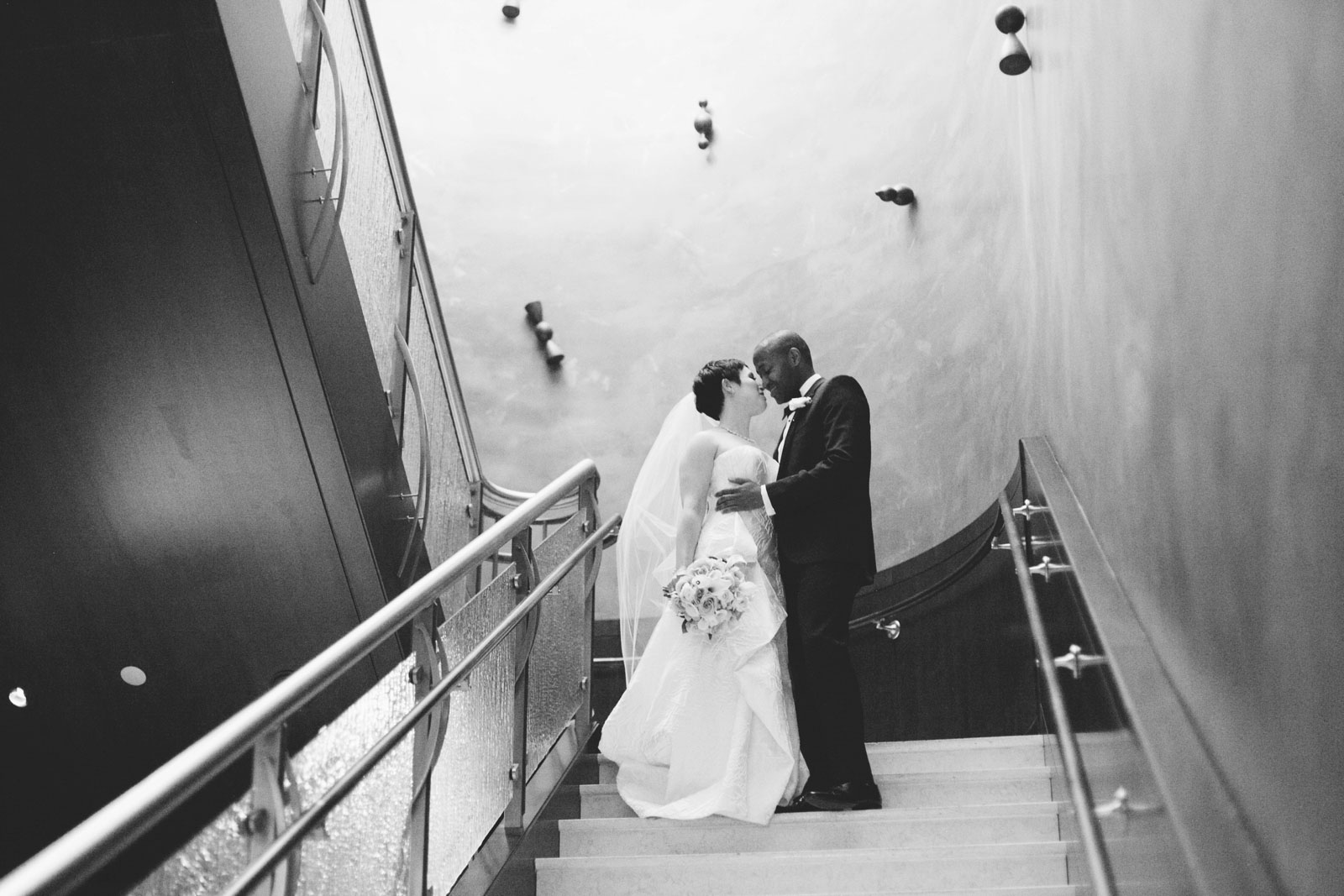 black and white intimate portrait of bride and groom holding each other close during first look