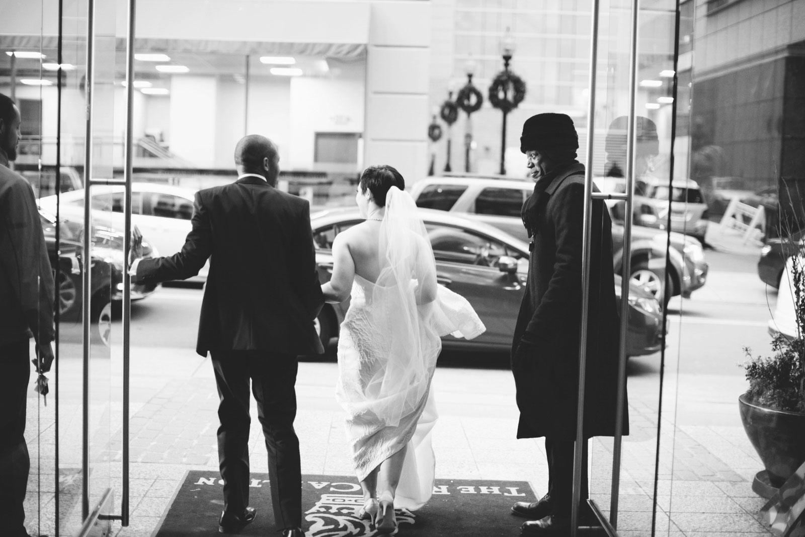black and white shot of bride and groom from behind walking through entryway to hotel