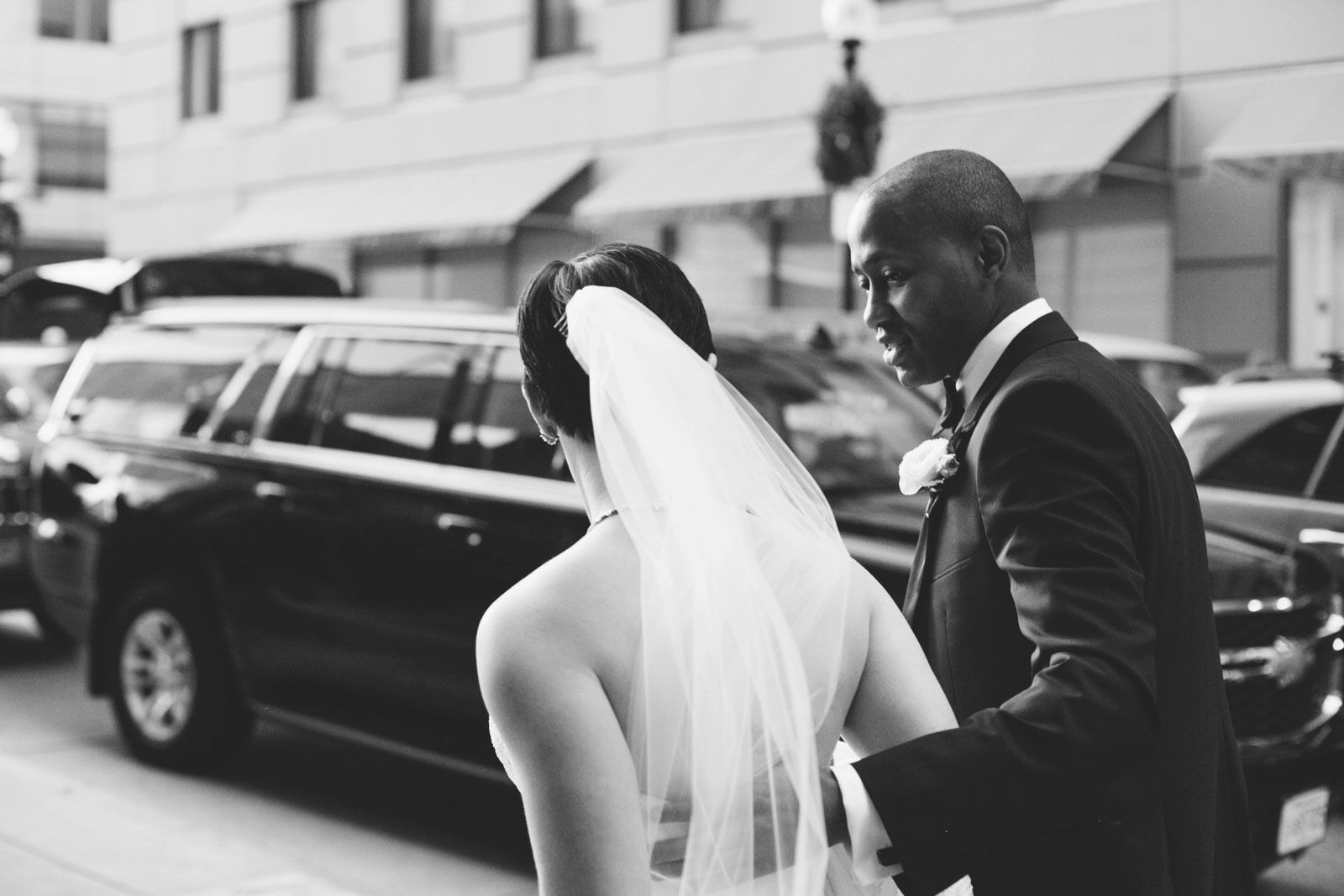 black and white candid of groom walking with bride down the streets of Boston