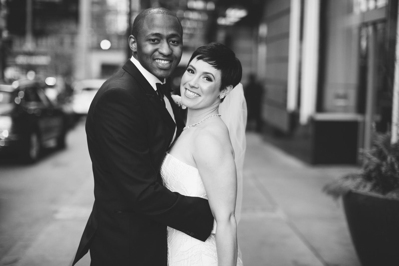 black and white intimate portrait of bride and groom on the streets of Boston in winter