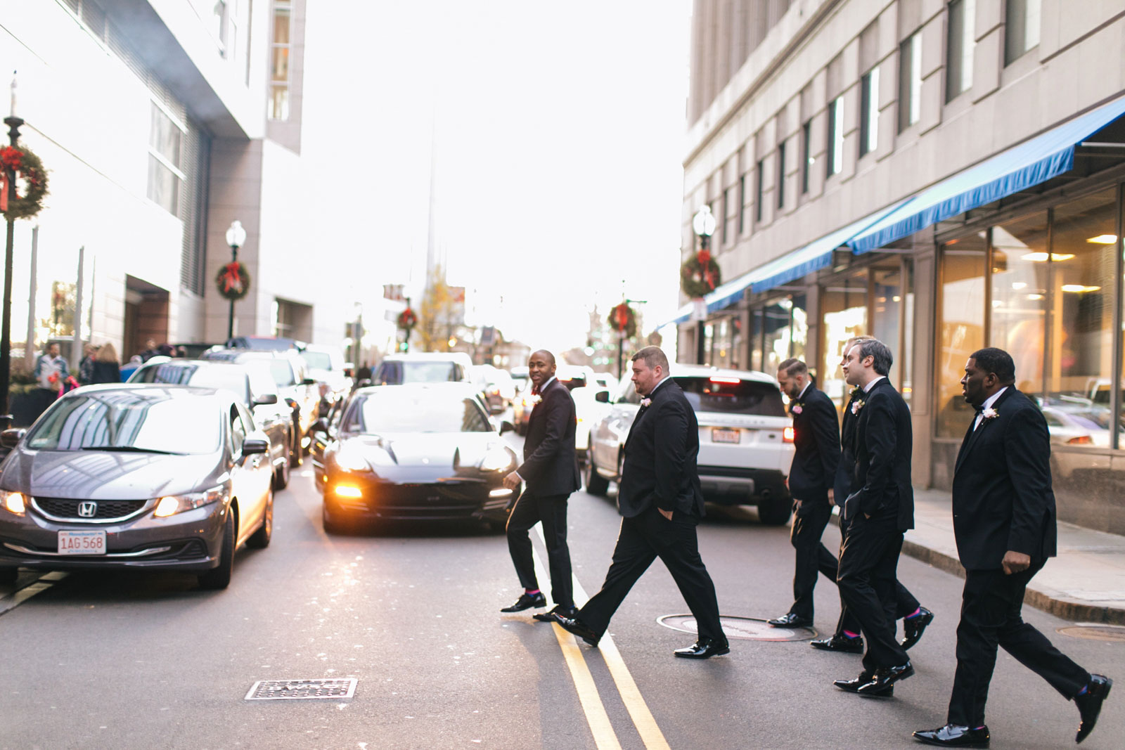 groomsmen crossing the street during portraits session on sunny afternoon winter wedding