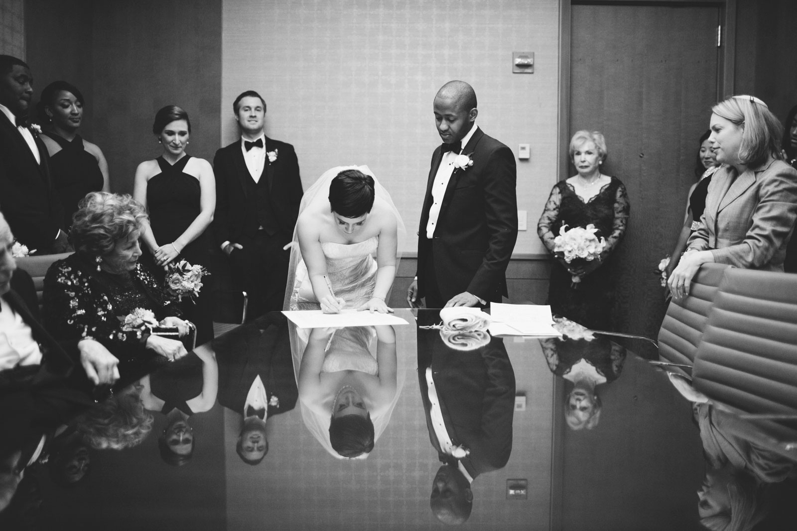 dramatic black and white shot bride signing ketubah surrounded by family with reflections in table