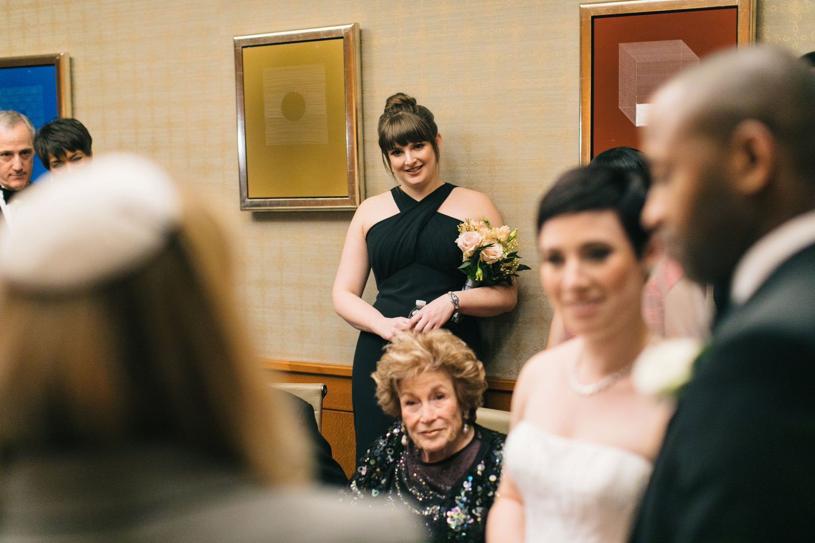 maid of honor listening to rabbi during ketubah signing at multicultural wedding ceremony