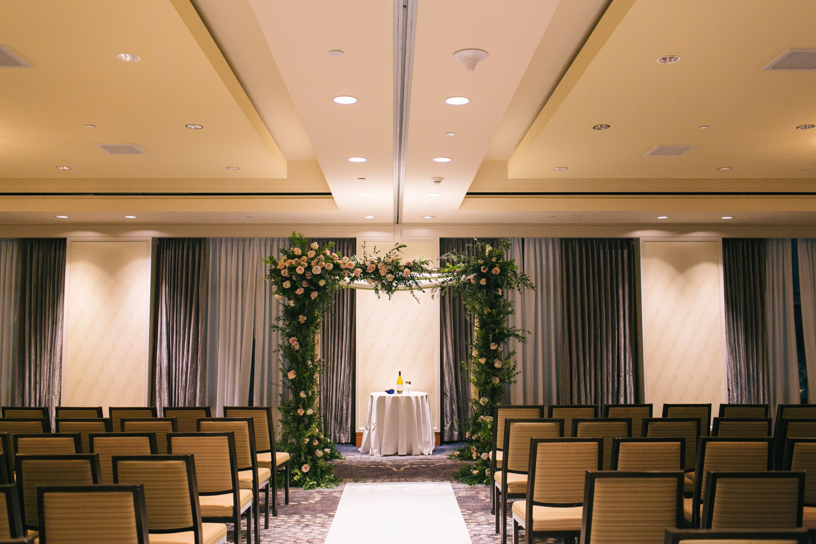 wedding ceremony room in Ritz-Carlton with chuppah decorated with roses and greenery