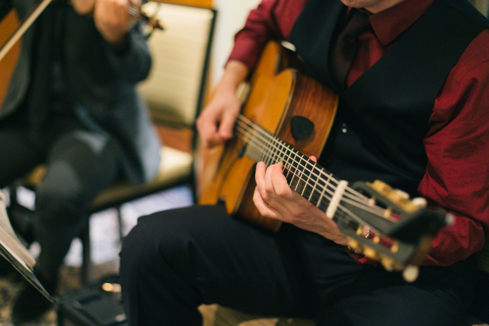 close up shot of guitarist playing as guests arrive for wedding ceremony at Ritz-Carlton hotel