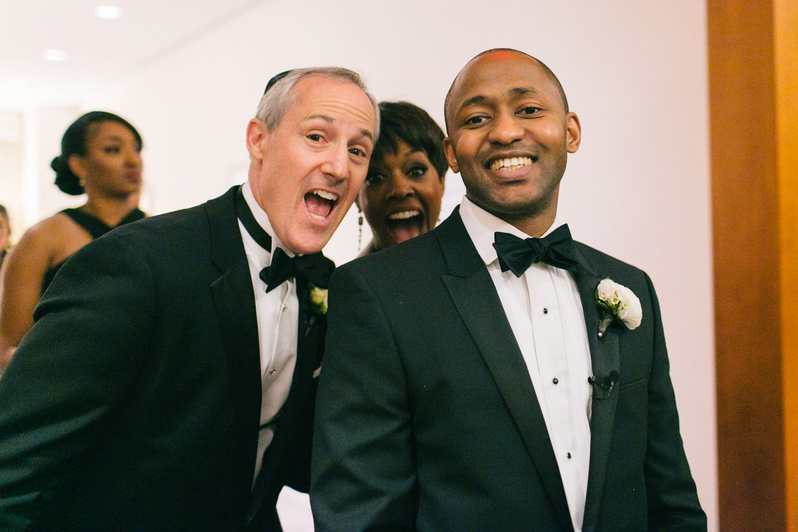Groom and in-laws laughing excitedly as they walk into ceremony at Ritz-Carlton