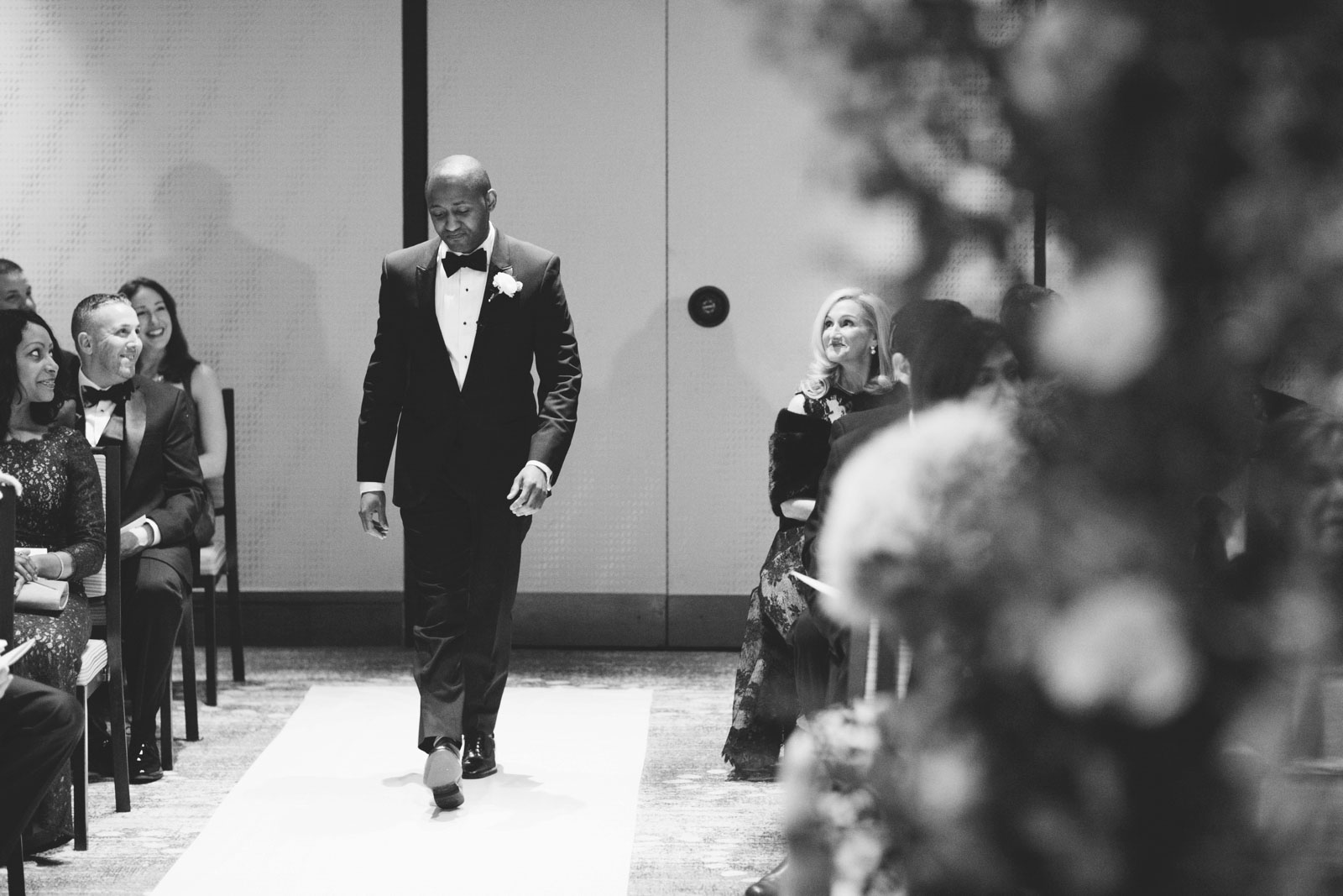 black and white shot of groom walking down aisle at multicultural wedding ceremony at Ritz-Carlton