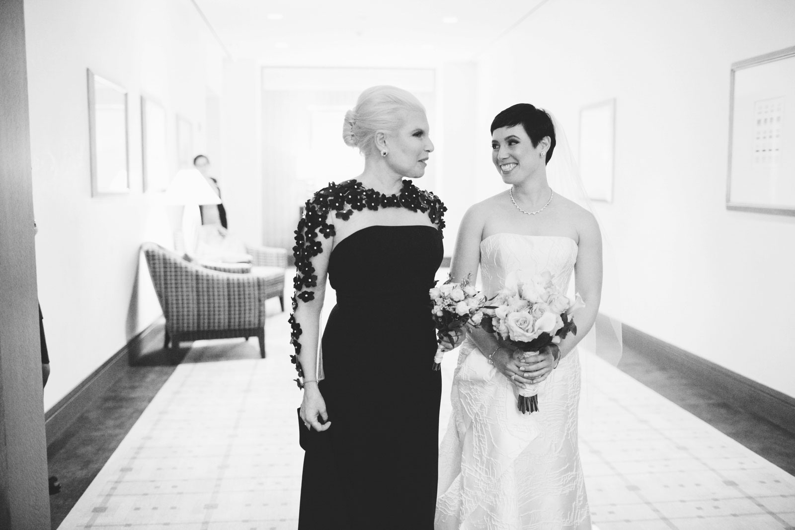 Bride and mother of bride smile at each other as they wait to walk down aisle together
