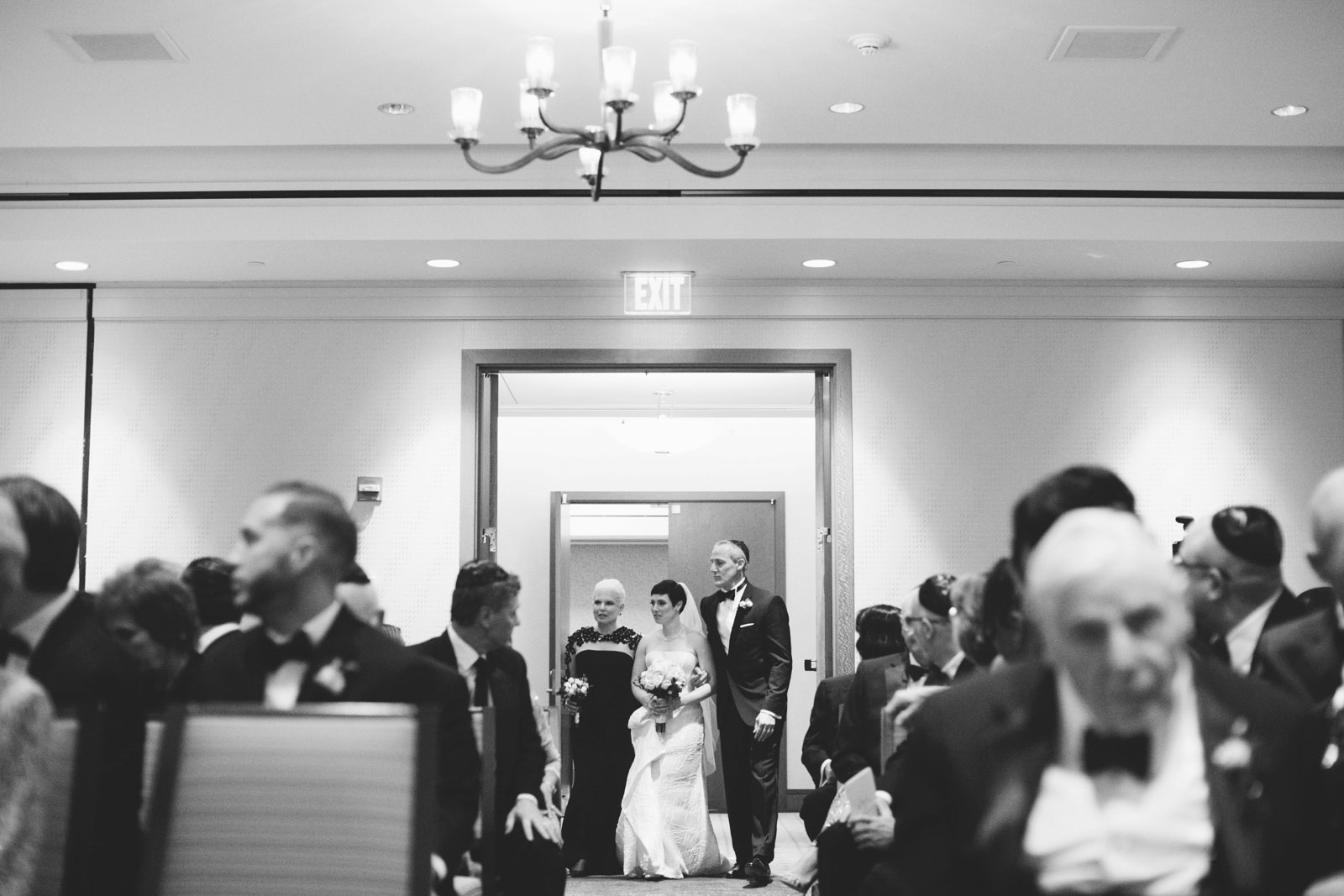 black and white shot of bride and her parents walking into ceremony room at Ritz-Carlton Boston