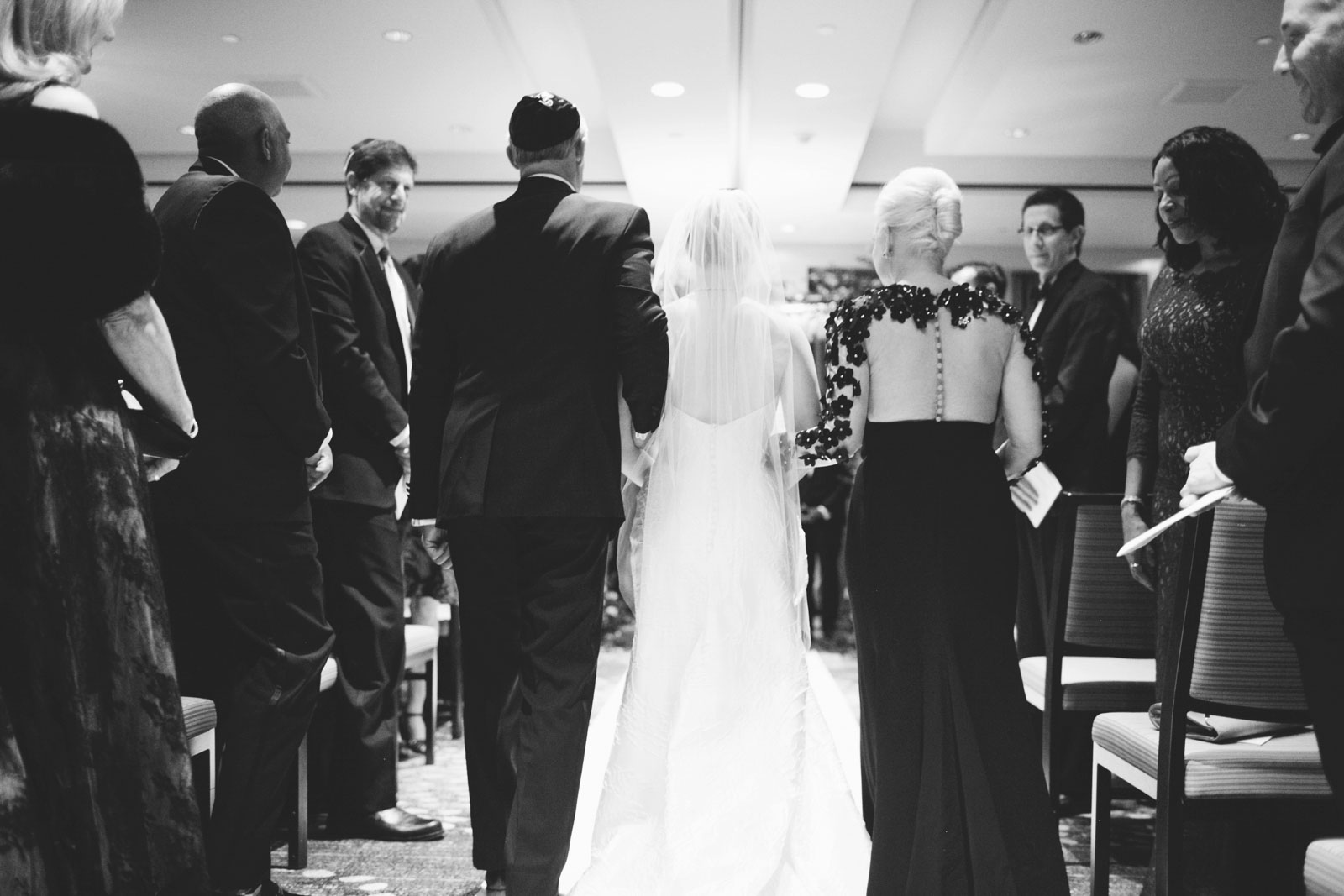 Bride and her parents walk down the aisle from behind in black and white