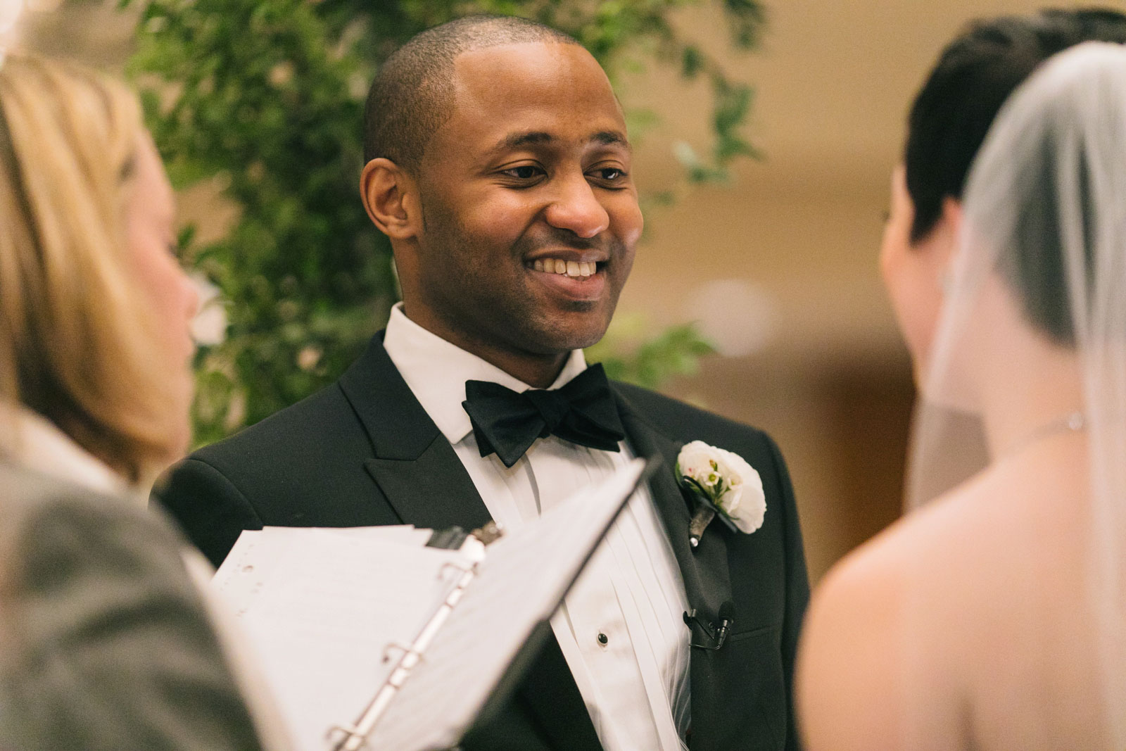 groom smiles at bride under chuppah during multicultural wedding ceremony at Ritz-Carlton Boston