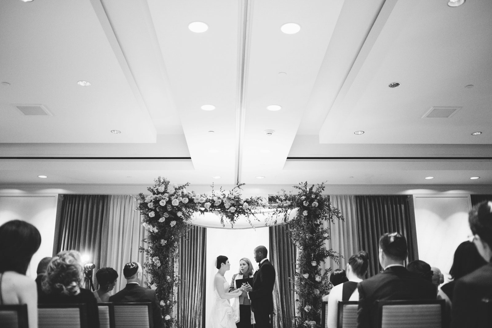 black and white shot of interracial wedding ceremony with dramatic perspective lines in ceiling